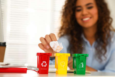 Young African-American woman throwing paper into mini recycling bin at table in office, focus on hand