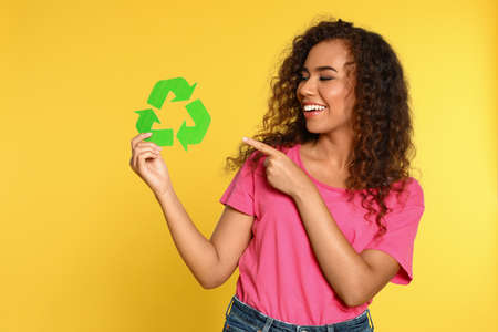 Young African-American woman with recycling symbol on yellow background