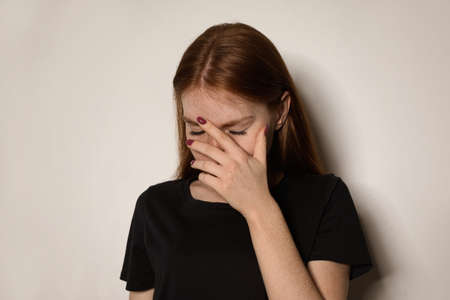 Young woman covering face against light background Stock Photo