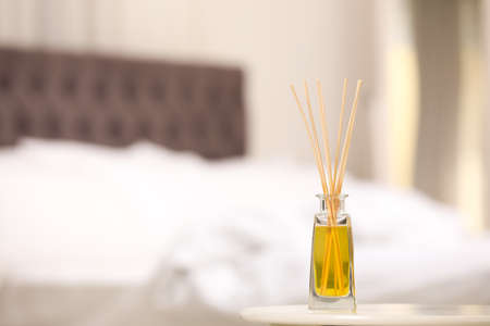 Reed air perfume with essential oil on table indoors. Space for text