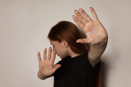 Young woman making stop gesture against light background, focus on hand Stock Photo