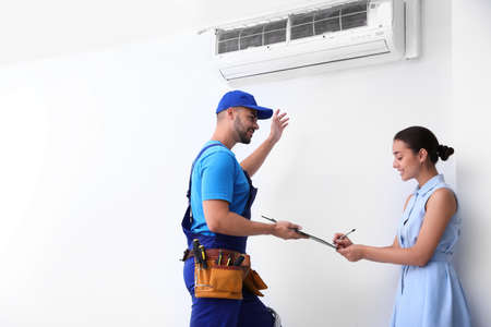 Professional technician speaking with woman about air conditioner indoors Foto de archivo