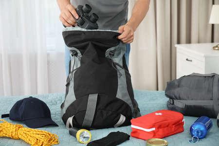 Hombre empacando diferentes equipos de campamento en la mochila en casa, primer plano Foto de archivo