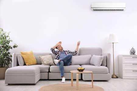 Jeune homme allumant le climatiseur avec télécommande à la maison