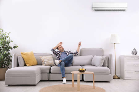 Young man switching on air conditioner with remote control at home