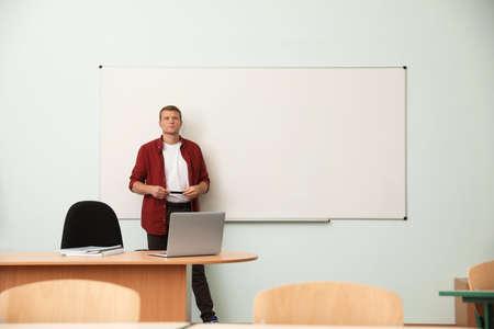 Male teacher near whiteboard in modern classroom