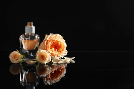 Elegant bottle of perfume and beautiful flowers on black background. Space for text