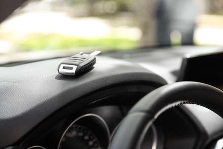 Car key on dashboard in auto against blurred background