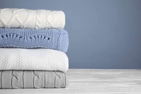 Stack of folded knitted sweaters on white wooden table against grey background, closeup. Space for text