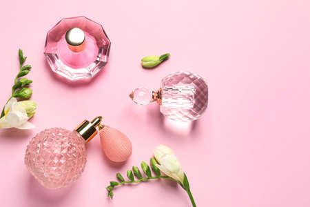 Flat lay composition with perfume bottles and flowers on light pink background, space for text Foto de archivo