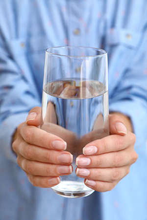 Woman holding glass of water, closeup. Refreshing drink Фото со стока