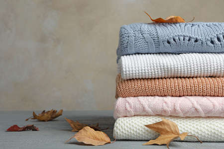 Stack of warm clothes and autumn leaves on wooden table against grey background. Space for text Stock Photo
