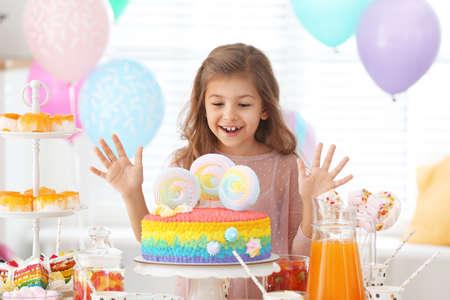 Niña feliz en la mesa con golosinas en la habitación decorada para la fiesta de cumpleaños