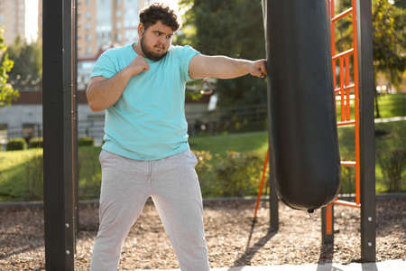 Young overweight man kicking heavy bag on sports ground