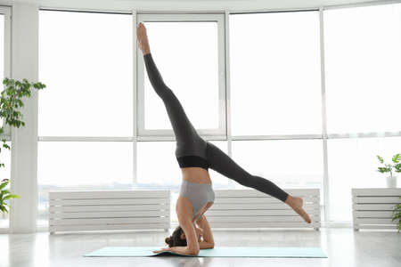 Young woman practicing supported headstand asana in yoga studio. Salamba Sirsasana pose