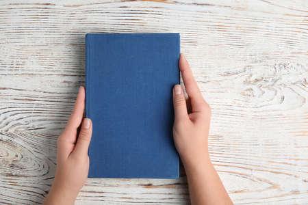 Frau mit Hardcover-Buch auf weißem Holzhintergrund, Ansicht von oben