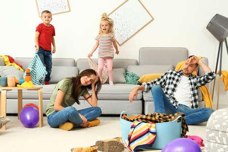 Sfrustrowani rodzice i ich psotne dzieci w zabałaganionym pokoju