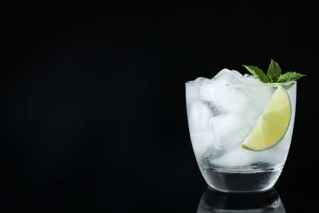 Glass of cocktail with vodka, ice and lime on black background. Space for text 写真素材