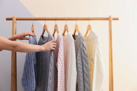 Woman choosing sweater on rack near color wall, closeup
