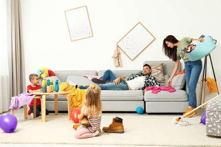 Mère épuisée essayant de nettoyer les dégâts causés par les enfants et père paresseux dans la chambre