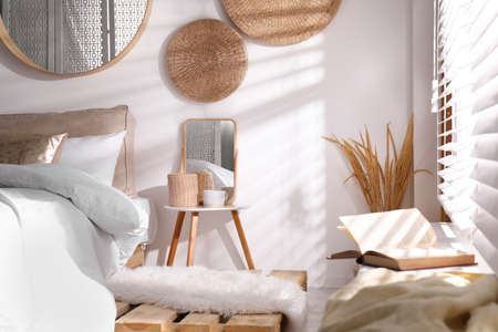 Stylish nightstand near bed in modern room interior
