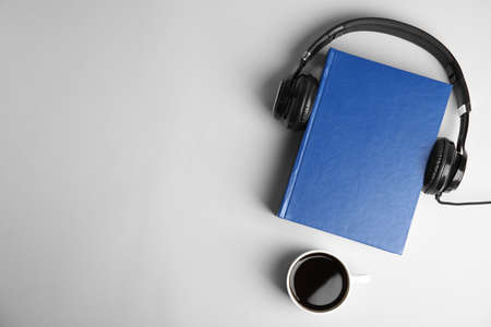 Modern headphones with hardcover book and coffee on light background, top view. Space for text Stock Photo
