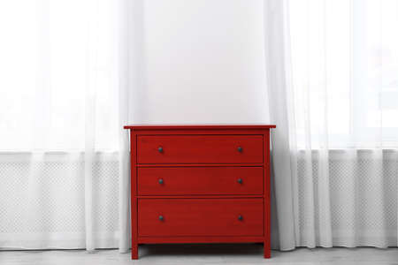 Red wooden chest of drawers near white wall indoors