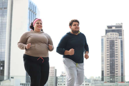 Overweight couple running together outdoors. Fitness lifestyle
