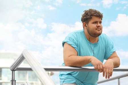Young overweight man leaning on railing outdoors