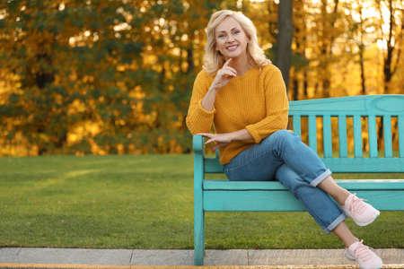Porträt einer glücklichen reifen Frau auf der Bank im Park