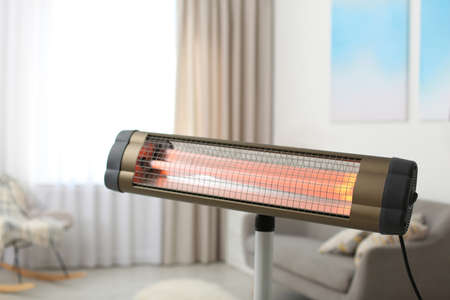 Modern electric infrared heater at home, closeup