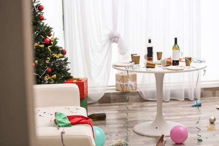Interno disordinato del soggiorno con l'albero di Natale. Caos dopo la festa