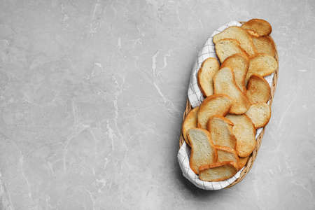 Basket with toasted bread on grey table, top view. Space for text