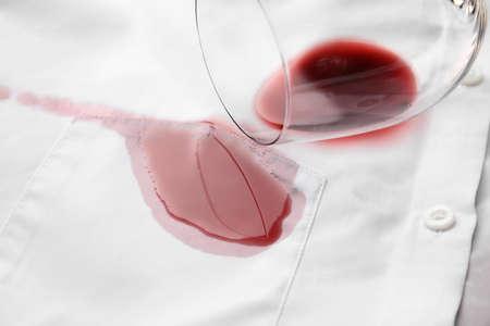 Verre renversé et vin rouge exquis renversé sur chemise blanche. Espace pour le texte