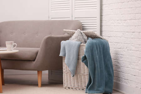 Basket with blankets and pillow near sofa indoors