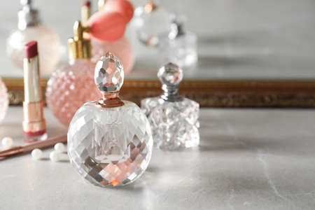 Different perfume bottles on dressing table, space for text Foto de archivo