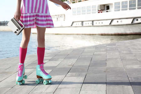 Young woman with vintage roller skates and radio on embankment, closeup view Foto de archivo