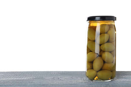 Jar of pickled olives on blue wooden table against white background. Space for text