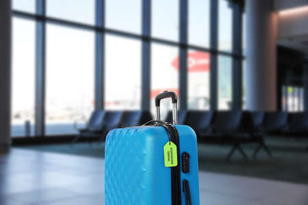 Blue suitcase with TRAVEL INSURANCE label in airport terminal