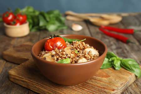 Delicious buckwheat porridge with mushrooms and tomato on wooden board Stock Photo