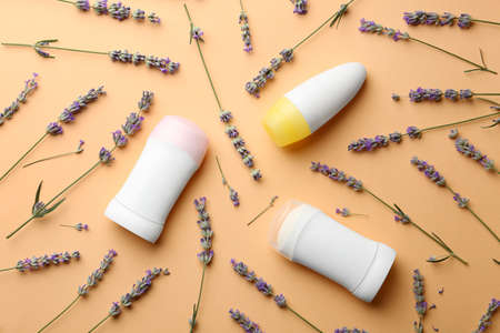 Different female deodorants and lavender flowers on apricot background, flat lay