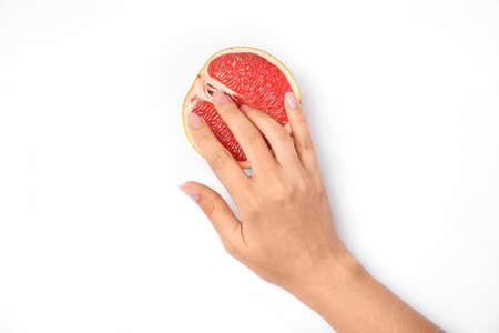 Young woman touching half of grapefruit on white background, top view. Sex concept Stock Photo