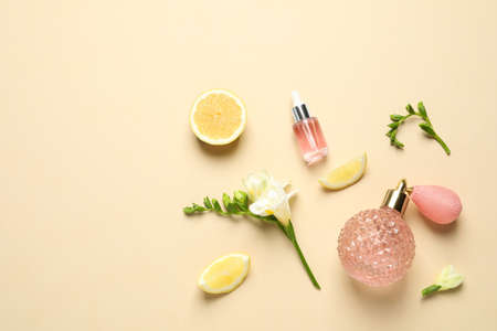 Flat lay composition with elegant perfume on beige background, space for text