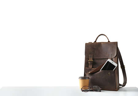 Composition with leather backpack, coffee and smartphone isolated on white
