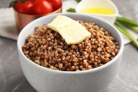 Bowl of buckwheat porridge with butter on table, closeup Stock Photo