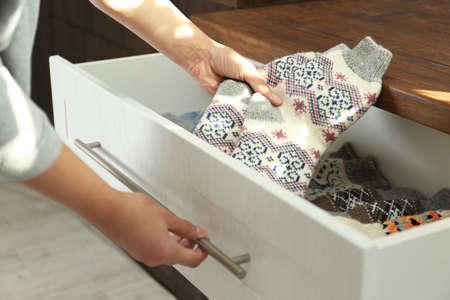 Donna che prende i calzini a maglia caldi dal cassetto all'interno, primo piano Archivio Fotografico