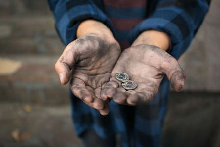 Poor homeless child with coins outdoors, closeup Reklamní fotografie