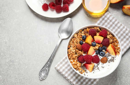 Healthy homemade granola with yogurt served on grey table, flat lay. Space for text Reklamní fotografie