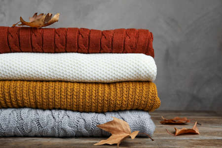 Stack of warm clothes and autumn leaves on wooden table against grey background Stock Photo
