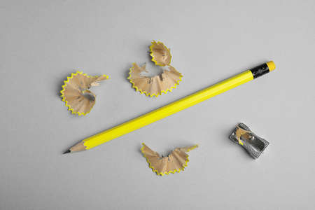 Pencil, sharpener and shavings on grey background, flat lay